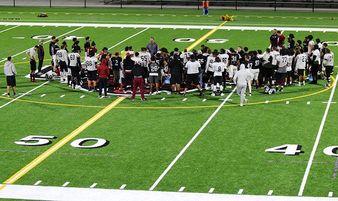The Central Washington football team huddles at midfield on the new Tomlinson Stadium turf in preparation for Saturday's game vs. West Texas A&M. Photo by Caleb Dunlop.