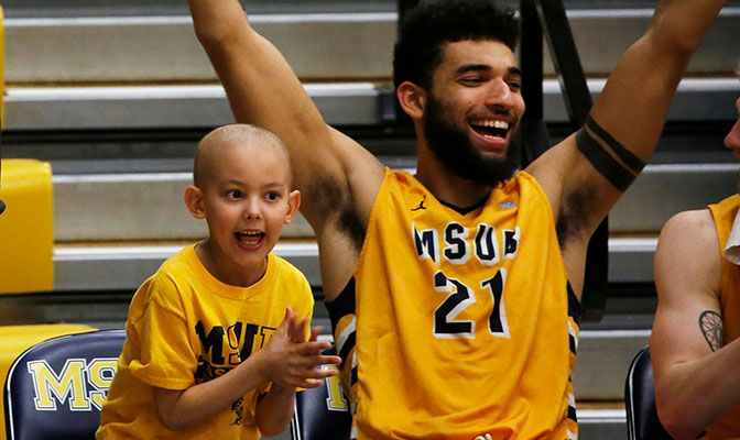 Elijah Salley celebrates on the MSUB bench with men's basketball player Kamal Tall. Salley is one of three youth