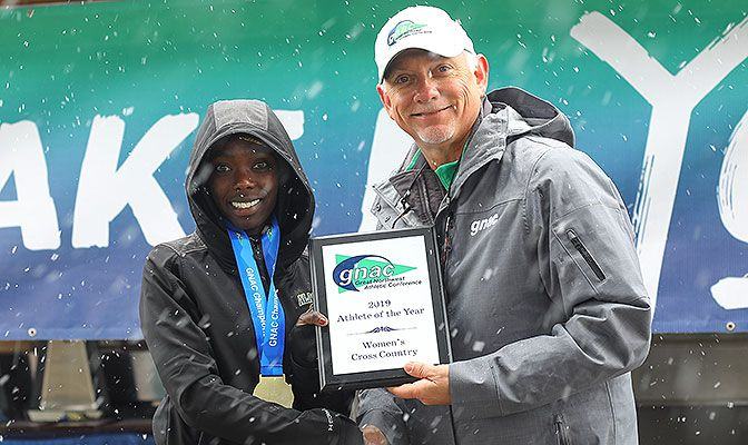 Alaska Anchorage's Emmah Chelimo, shown with GNAC commissioner Dave Haglund, repeated as individual champion in a time of 21:31.9. Photo by Jenna Martin.