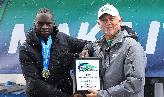 Alaska Anchorage's Felix Kemboi, here with GNAC commissioner Dave Haglund, won the individual title in a time of 24:44. Photo by Jenna Martin.
