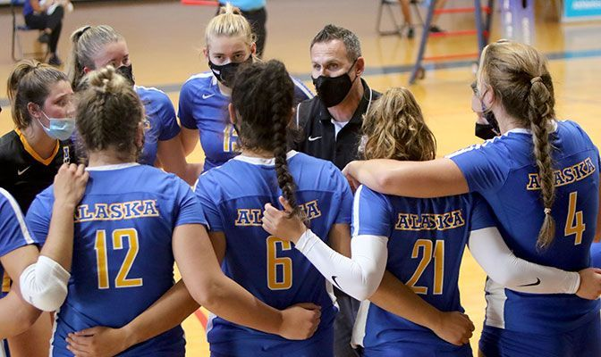 The Alaska volleyball team huddles around head coach Brian Scott during a timeout. The Nanooks are yet to drop a set in GNAC play this season. Photo by Miles Jordan.