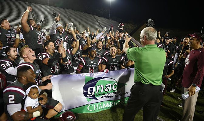 Conference commissioner Dave Haglund presents the GNAC championship trophy to Azusa Pacific following the Cougars' 44-7 win over Central Washington on Saturday.
