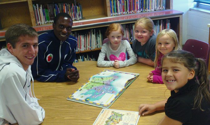 Georgia Regents runner Jaiden Brandt (left) and assistant coach Pardon Ndhlovu pose with students at Pasadena Park Elementary during Thursday's community engagement activities.