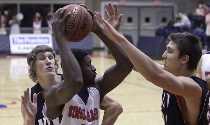 NNU's Keith Moilanen (left) and Kevin Rima (right) surround SFU's Ibrahim Appiah (Photo by Ron Hole)