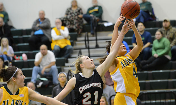 Megan Hingston (21), in action in a game earlier this season in Anchorage, keyed a GNAC record rebounding performance by Northwest Nazarene Thursday (Photo by Sam Wassom)
